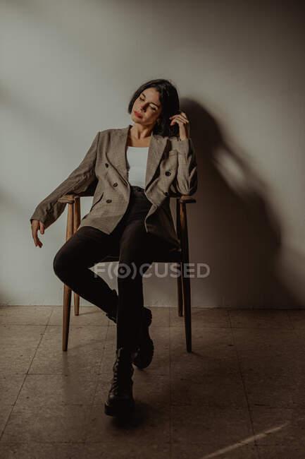 Donna rilassata che indossa abiti alla moda seduta sulla sedia mentre tocca i capelli con gli occhi chiusi — Foto stock