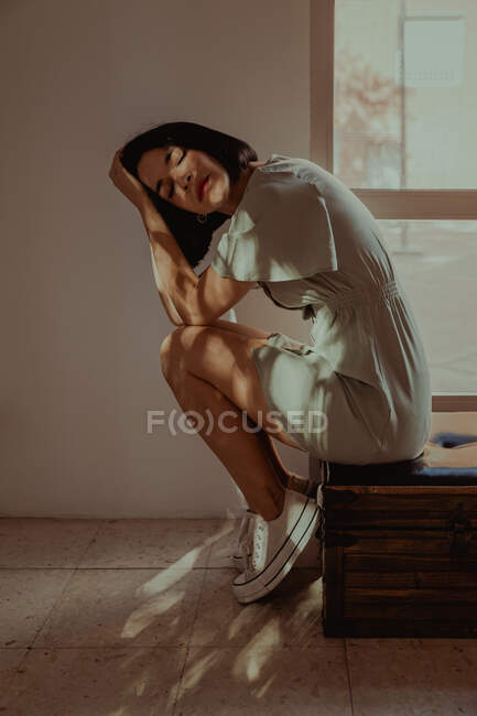 Side view of tender female leaning on hands while sitting with closed eyes on stool in room lit by sunlight — Stock Photo