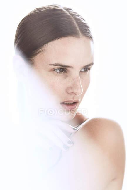 Серйозна жінка з гримом і веснянками на носі м'яко торкається шкіри і дивиться геть — стокове фото