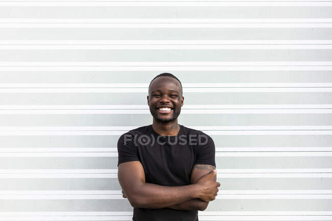 Content African American man in black t shirt standing looking at camera on light background — Stock Photo