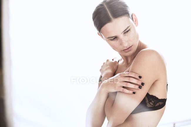 Sinnliche Frau mit Tätowierung mit BH am Hals steht im Studio gegen Weiß — Stockfoto