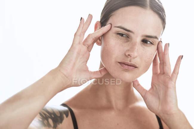 Mulher séria com maquiagem e sardas no nariz tocando suavemente a pele e olhando para longe — Fotografia de Stock