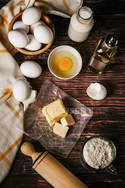 Top view of various ingredients for baking near cooking tools placed on wooden table in kitchen — Stock Photo