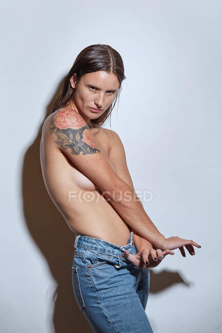 Side view of young female with bare breasts wearing casual jeans standing against gray background — Stock Photo