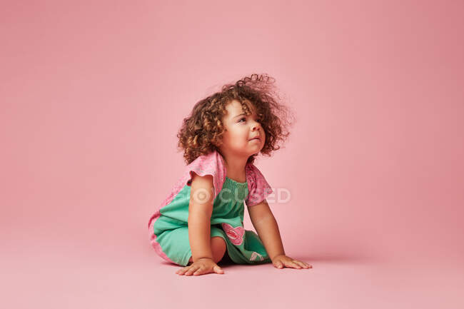 Adorable toddler child in dress with curly hair having a tantrum looking away leaning sitting on the on floor — Stock Photo