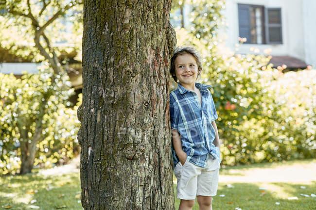 Menino elegante feliz em shorts e camisa quadriculada apoiada no tronco da árvore e sorrindo enquanto descansa no quintal no dia ensolarado — Fotografia de Stock