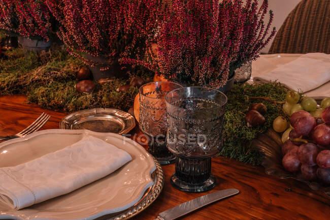 Hohe Winkel von Kristallgläsern in der Nähe von Teller und Besteck auf Tisch mit Trauben Calluna vulgaris Blumen und Granatapfel dekoriert — Stockfoto