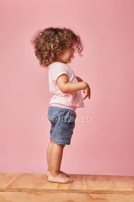Vista laterale di affascinante bambino scalzo in t-shirt e pantaloncini di jeans con i capelli ricci guardando altrove mentre in piedi giocando sulla piattaforma di legno — Foto stock