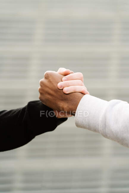 Side view of unrecognizable stylish young diverse male friends in trendy outfits standing on paved street in city and shaking hands — Stock Photo