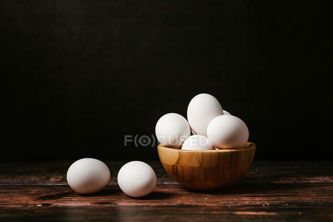 Uncooked eggs in bowl placed on wooden table in dark background for cooking breakfast — Stock Photo