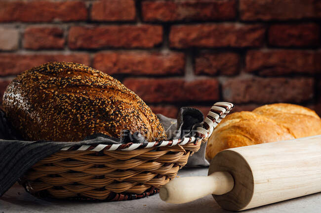 Delicious wholegrain bread in straw basket on table — Stock Photo