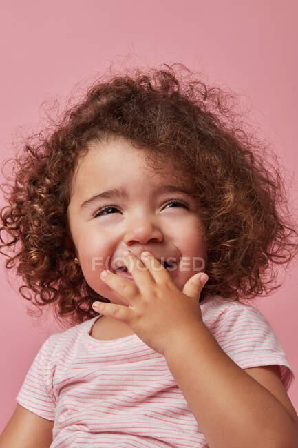 Nettes fröhliches Kleinkind Mädchen mit lockigem Haar in lässiger Kleidung bedeckt Mund mit der Hand beim Wegschauen lächelnd auf rosa Hintergrund — Stockfoto