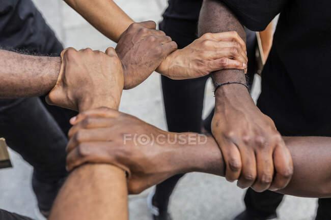 З верху врожаю анонімні афроамериканські партнери трималися за руки і демонстрували єдність у місті. — стокове фото