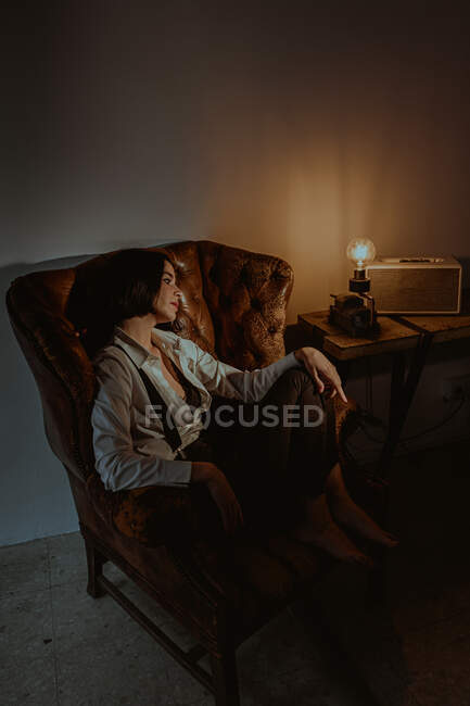 Side view of serene female relaxing in old leather armchair in vintage room with glowing light bulb and looking away — Stock Photo