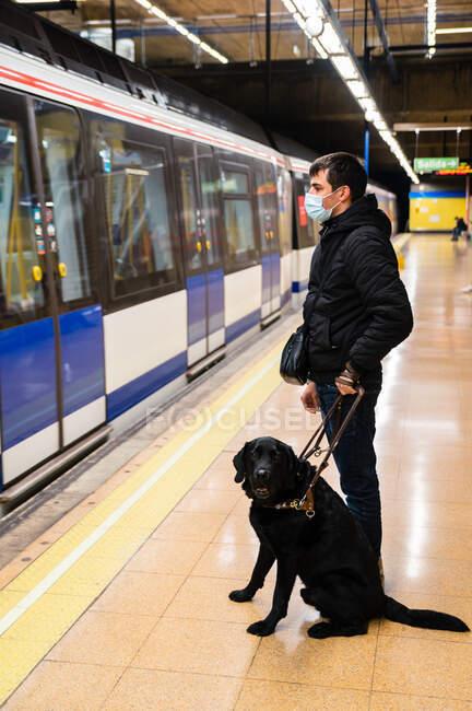 Vista lateral de ángulo bajo cuerpo completo de macho ciego anónimo en máscara de pie con perro guía en la correa en la plataforma - foto de stock