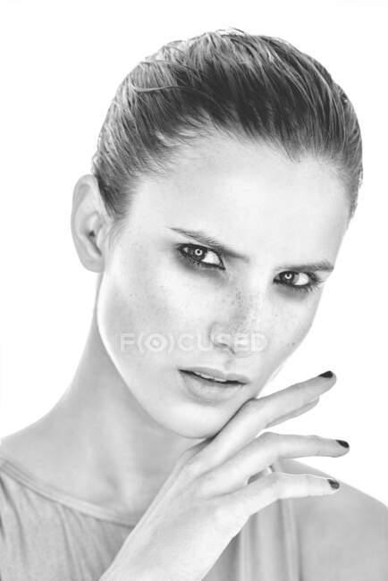 Черно-белая серьезная женщина с макияжем и веснушками на носу нежно касается кожи и смотрит в камеру — стоковое фото