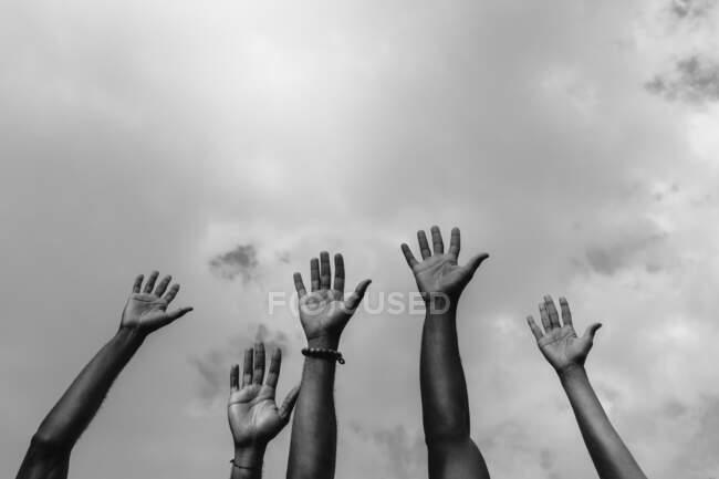 D'en bas des guerriers anonymes afro-américains de justice sociale levant les armes blanc luttant pour les droits sociaux pendant la manifestation — Photo de stock