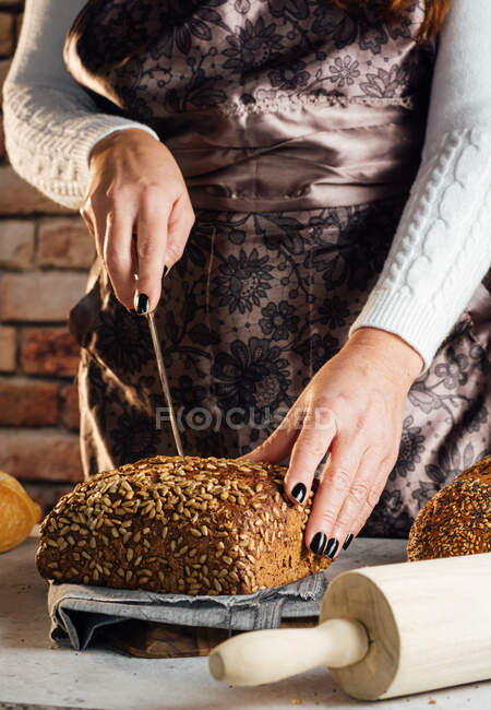 Crop anonymous female baker with knife cutting loaf of fresh bread with sunflower seeds on table in bakehouse — Stock Photo