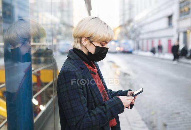 Vista lateral calma jovem fêmea em casaco quente e máscara protetora navegando telefone celular moderno enquanto estava na rua da cidade no dia de inverno em Madrid, Espanha — Fotografia de Stock
