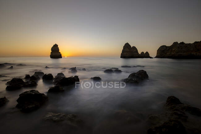 From above picturesque view of rocky formations in ocean coastline under sunset sky in Praia do Camilo, Algarve Portugal — Stock Photo