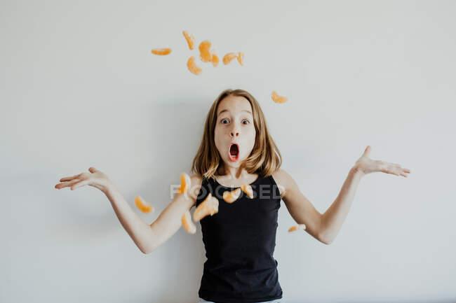 Bambino stupito in abiti casual gettando fette di mandarino e spalle scrollate di spalle con la bocca aperta mentre si diverte sullo sfondo bianco — Foto stock