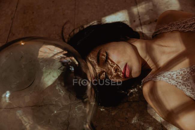 De cima da fêmea doce com olhos fechados e no vestido que jaz no soalho perto da garrafa de vidro no quarto com a luz solar — Fotografia de Stock