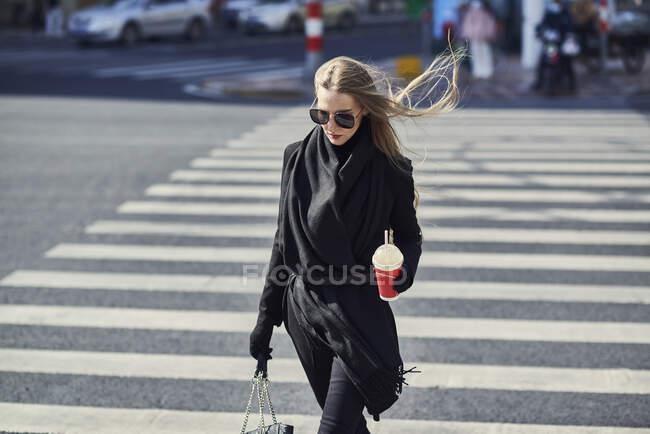 Молода жінка в модному чорному одязі і сонцезахисних окулярах гуляє по перехресті з одноразовою чашечкою напоїв в місті. — стокове фото