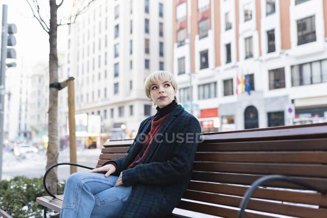 Jovem atraente com cabelo curto em casaco quente sentado no banco na rua contemporânea da cidade no final do dia de outono em Madrid, Espanha — Fotografia de Stock