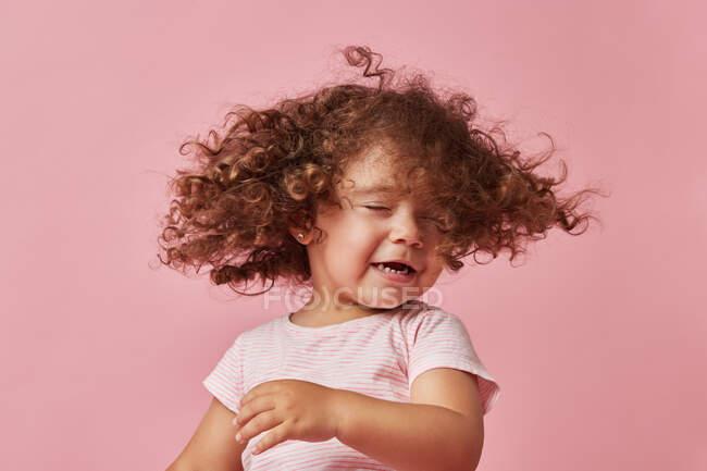 Menina criança alegre bonito com cabelo encaracolado em roupas casuais balançando a cabeça com os olhos fechados no fundo rosa — Fotografia de Stock