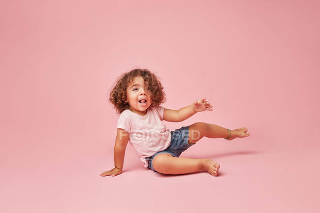 Cute cheerful toddler girl with curly hair in casual clothes having fun looking away smiling while sitting on pink background — Stock Photo