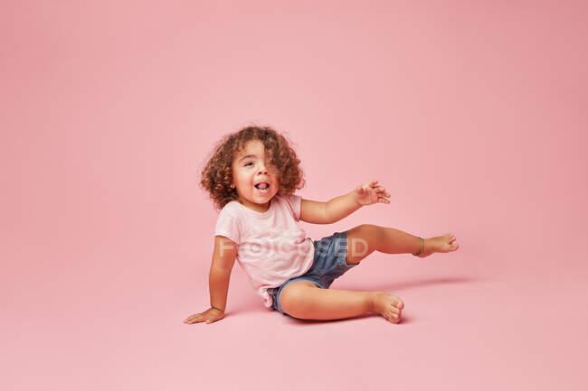 Menina da criança alegre bonito com cabelo encaracolado em roupas casuais se divertindo olhando para longe sorrindo enquanto sentado em fundo rosa — Fotografia de Stock