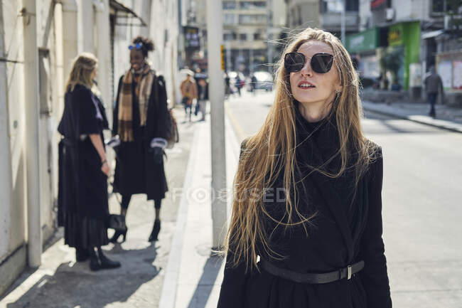 Young blond female in stylish black apparel and sunglasses on city roadway against unrecognizable diverse female friends in back lit — Stock Photo