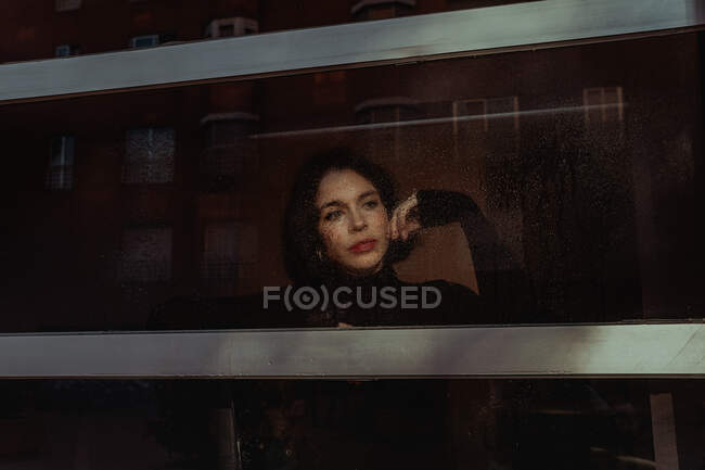 Through glass of thoughtful female standing near window and observing street while looking away — Stock Photo