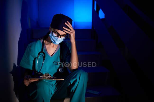 Médico femenino pensativo en uniforme sentado en las escaleras y examinando el informe médico mientras toca la cabeza en el fondo de la luz de neón azul - foto de stock