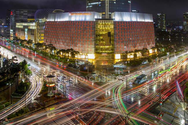 Corea del Sur - 2 de julio de 2018: Desde arriba del centro comercial iluminado Lotte World Mall ubicado cerca de la carretera con luces de colores en exposición prolongada - foto de stock