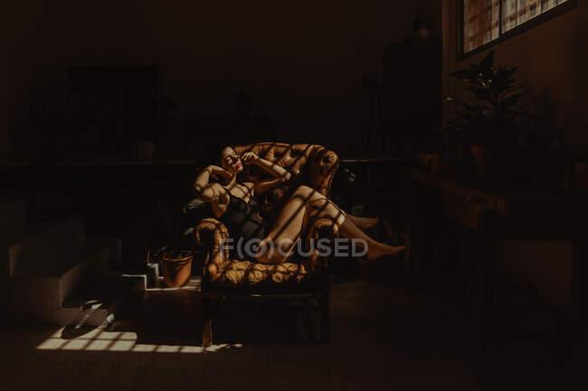 Vista laterale di tranquilla donna in camicia da notte seduta in poltrona di pelle illuminata dalla luce del sole e rilassante con gli occhi chiusi — Foto stock