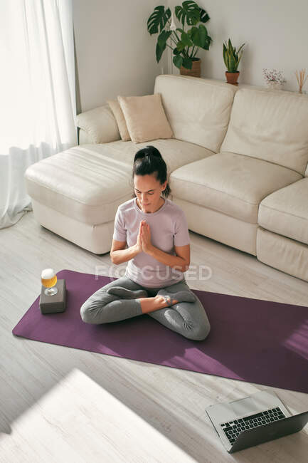 From above of tranquil female sitting in Lotus pose on mat with glass of beer and laptop while doing yoga and meditating at home — Stock Photo