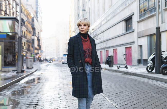 Attractive positive female in trendy wear and warm coat standing with hands in pockets on snowy city street and looking away on clear winter day in Madrid, Spain — Stock Photo