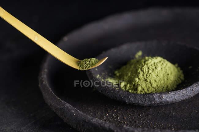 Colher com folhas secas de chá matcha em utensílios de mesa pretos para cerimônia oriental tradicional — Fotografia de Stock