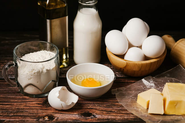 Various ingredients for baking placed on wooden rustic table in kitchen — Stock Photo
