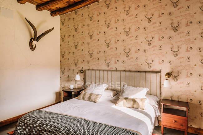Внутрішня частина стильної спальні з зручним ліжком, покритим ковдрою біля вікна, прикрашеного фіранками. — стокове фото