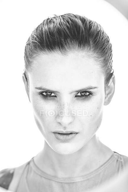 Black and white of serious female with makeup and freckles on nose gently and looking at camera — Stock Photo