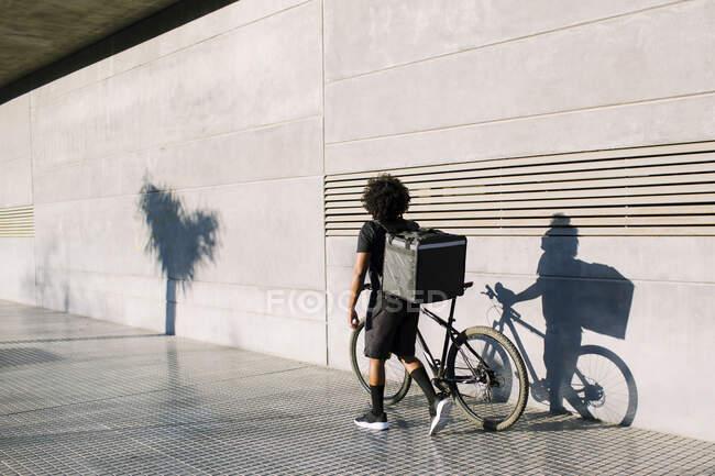 Visão traseira do piloto de entrega preto com caixa e bicicleta andando no pavimento da cidade contra a parede com sombra enquanto olha para longe na luz do sol — Fotografia de Stock