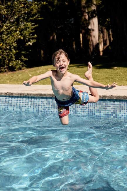 Allegro ragazzino senza maglietta che urla mentre salta in piscina durante le vacanze estive in campagna — Foto stock