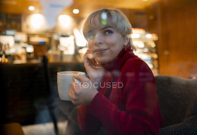 Через стеклянный боковой вид улыбается молодая женщина в уютном красном свитере наслаждаясь ароматным горячим напитком и трогательным лицом, сидя на удобном кресле в кафетерии и мечтательно глядя в сторону — стоковое фото
