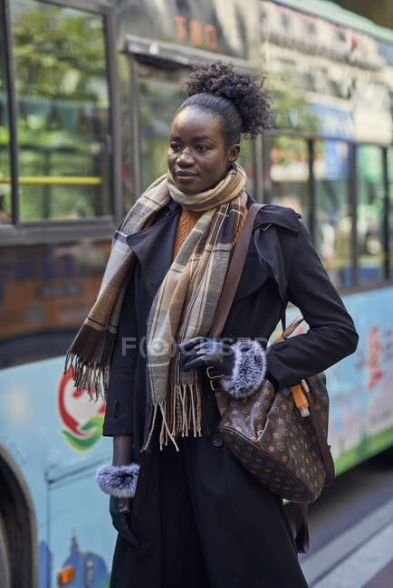 Young trendy ethnic female in coat and scarf with Afro hair bun looking forward on urban pavement — Stock Photo