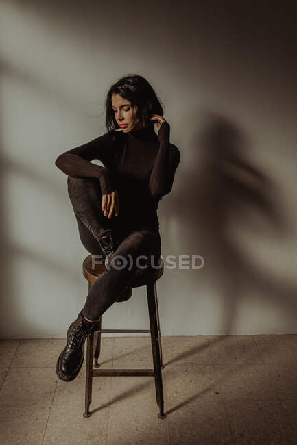 Slim female in black outfit sitting on wooden stool with raised legs in room against white wall — Stock Photo