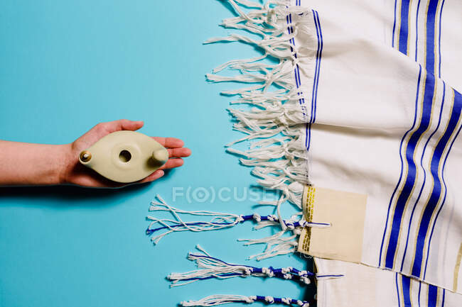 Top view of crop anonymous tourist with oval shaped item with hole near scarf with ornament representing travelling by sea concept — Stock Photo