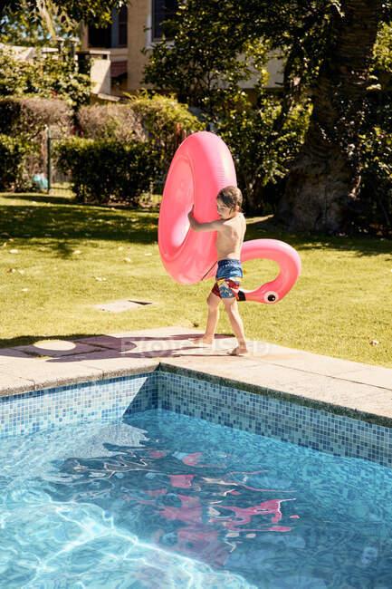 Вид сбоку анонимного бесшабашного мальчика, несущего розовый фламинго во время прогулки по бассейну во дворе отеля в солнечный день — стоковое фото