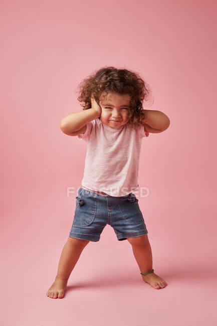 Corpo inteiro de criança descontente em vestuário casual com cabelos cacheados cobrindo orelhas enquanto olha para a câmera — Fotografia de Stock